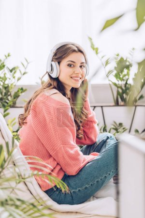 attractive young woman listening music in headphones and looking at camera while sitting surrounded by green plants at home