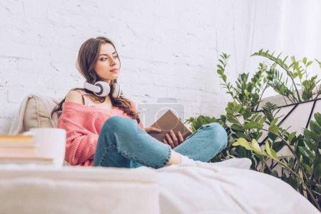 Photo pour Chère jolie femme regardant loin tout en étant assis avec les jambes croisées et tenant livre - image libre de droit
