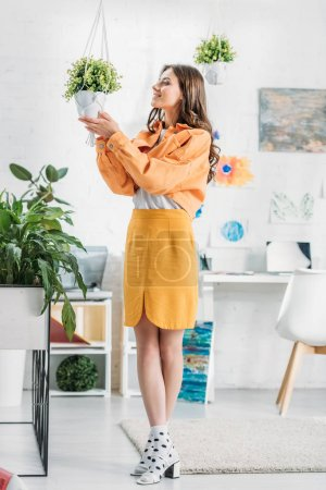Photo for Trendy woman in orange clothing touching flowerpot with green plant - Royalty Free Image