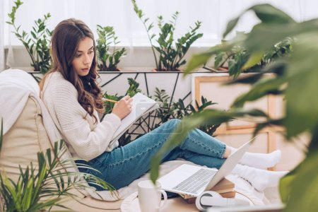 Photo for Selective focus of attentive young woman writing using laptop and writing in notebook while sitting near green plants at home - Royalty Free Image