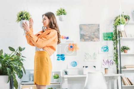 Photo for Beautiful woman in orange clothing touching hanging flowerpot in spacious room - Royalty Free Image