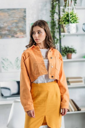 Photo for Pensive pretty girl in orange clothing looking away while standing near rack with books and plants - Royalty Free Image