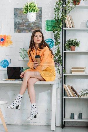 Foto de Chica pensativa sentada en el escritorio cerca de la computadora portátil con pantalla en blanco, sosteniendo la taza desechable y mirando hacia otro lado - Imagen libre de derechos