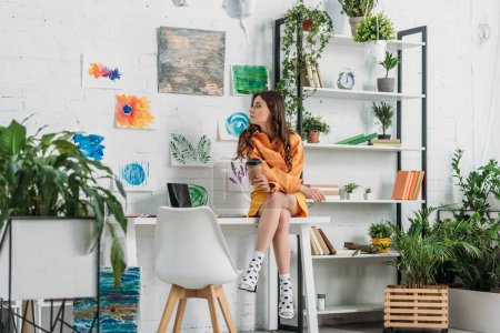 Photo for Attractive girl sitting on desk and holding paper cup in room decorated with green plants and paintings on wall - Royalty Free Image