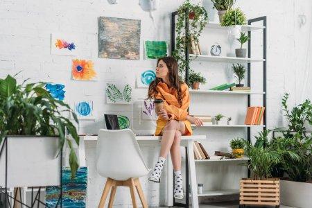 Photo pour Fille attirante s'asseyant sur le bureau et retenant la tasse de papier dans la salle décorée avec les usines et les peintures vertes sur le mur - image libre de droit