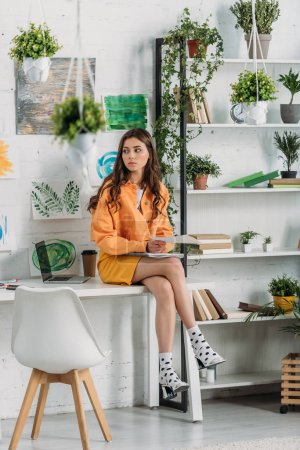 Photo for Pensive young woman sitting on desk in room decorated with green plants and paintings on wall - Royalty Free Image
