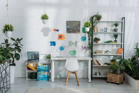 Photo for Light spacious room decorated with plants and paintings on white wall with racks, desk and chair - Royalty Free Image