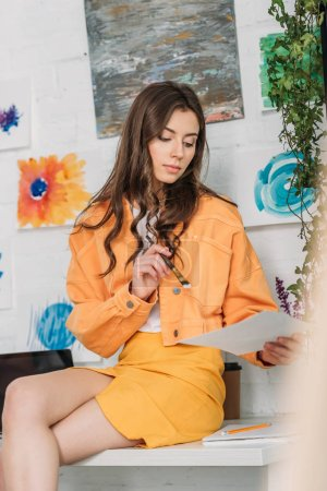 Photo for Selective focus of dreamy girl holding paintbrush and paper while sitting on desk near paintings on wall - Royalty Free Image