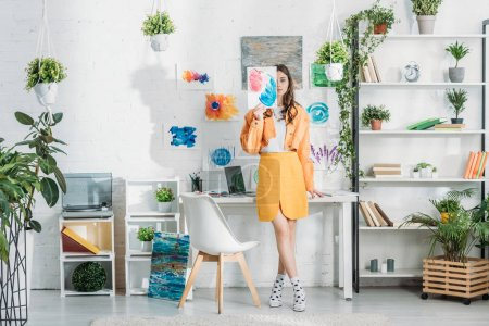 Foto de Trendy young woman covering face with painting while standing in spacious room decorated with green plants and drawings on white wall - Imagen libre de derechos