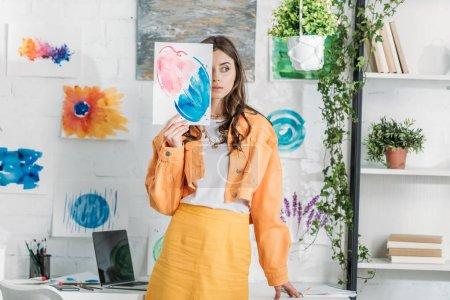 Photo pour Belle fille cachant visage derrière la peinture tout en se tenant dans une chambre spacieuse décorée avec des plantes vertes et des dessins sur mur blanc - image libre de droit