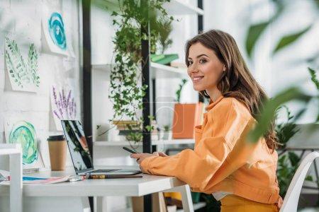 Foto de Enfoque selectivo de la mujer joven sonriente usando el teléfono inteligente mientras está sentado en el escritorio cerca de la computadora portátil - Imagen libre de derechos