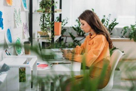 Foto de Enfoque selectivo de la joven pensativa sentada en el escritorio cerca de la computadora portátil y el uso de teléfono inteligente - Imagen libre de derechos