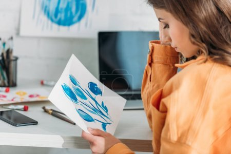 Photo for Pensive young woman sitting at desk and looking at painting with blue flowers - Royalty Free Image
