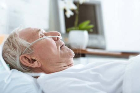 Photo pour Side view of senior man in coma on bed in hospital - image libre de droit