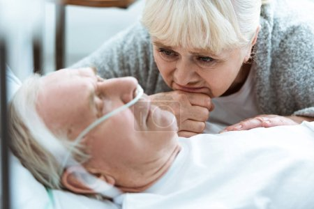 Photo pour Femme aînée triste avec le mari dans le coma dans la clinique - image libre de droit
