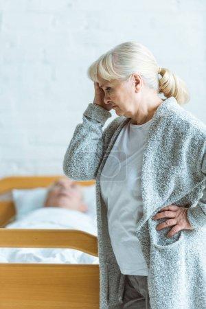 Photo pour Femme âgée bouleversée et homme dans le coma dans la clinique - image libre de droit