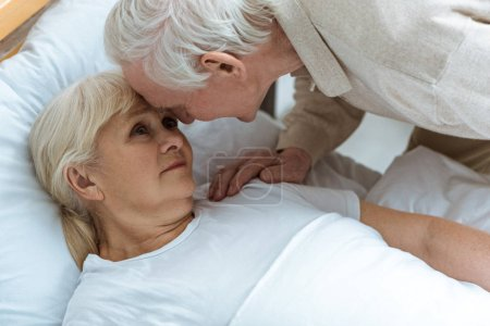 Photo for Sick senior woman with husband looking at each other in ward in clinic - Royalty Free Image