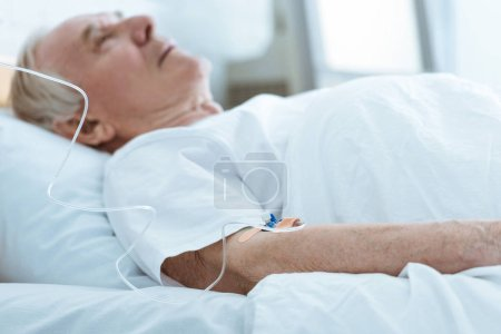 Photo for Selective focus of senior unconscious man lying on bed in hospital - Royalty Free Image