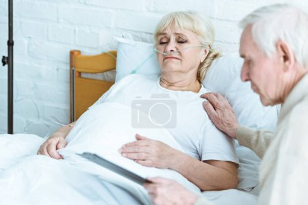 Photo for Senior man holding clipboard with sick wife in clinic - Royalty Free Image