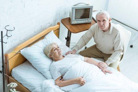 Photo pour Vue aérienne de la femme aînée malade avec le mari dans la clinique - image libre de droit