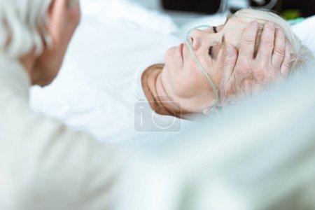 Photo pour Vue recadrée de l'homme aîné caressant la femme dans le coma dans la clinique - image libre de droit