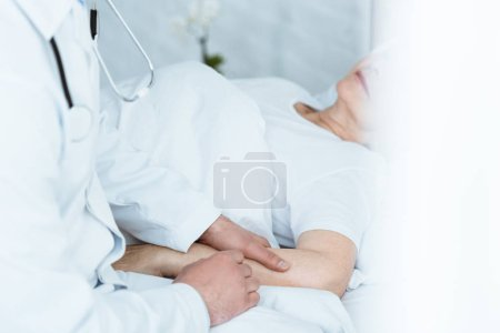 Photo for Partial view of doctor in white coat and senior patient in clinic - Royalty Free Image