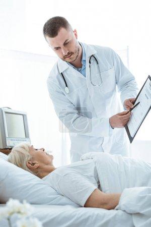 Photo pour Médecin avec le presse-papiers et la femme aînée malade se trouvant sur le lit - image libre de droit