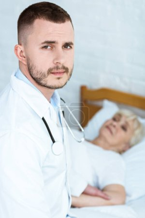 Photo for Doctor in white coat and sick senior patient lying on bed - Royalty Free Image