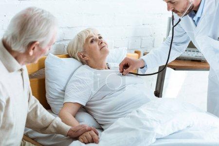 Photo pour Vue partielle du docteur examinant le patient malade et l'homme aîné - image libre de droit