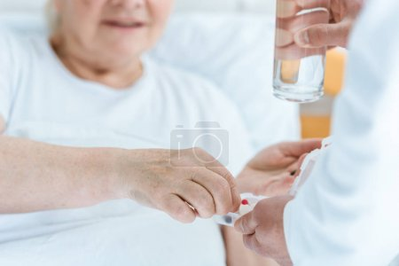 Photo for Partial view of doctor giving medicine and glass of water to patient - Royalty Free Image