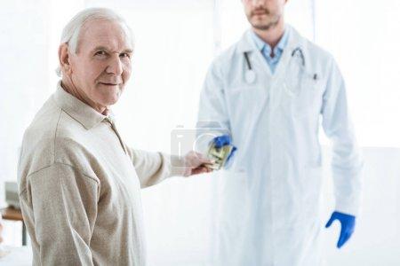 Photo pour Souriant senior homme donnant pot de vin au médecin sur blanc - image libre de droit