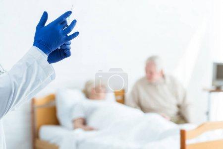 Photo pour Vue partielle du docteur dans la seringue de fixation de gants de latex, patient malade et homme aîné dans la clinique - image libre de droit