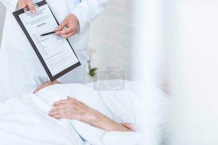 Photo pour Vue partielle du docteur retenant le presse-papiers et le stylo et le patient malade dans la clinique - image libre de droit