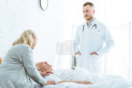 Photo for Serious doctor standing with hands in pockers near ill patient and senior woman in clinic - Royalty Free Image