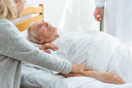 Photo pour Vue partielle du docteur, du patient malade et de la femme aînée dans la clinique - image libre de droit