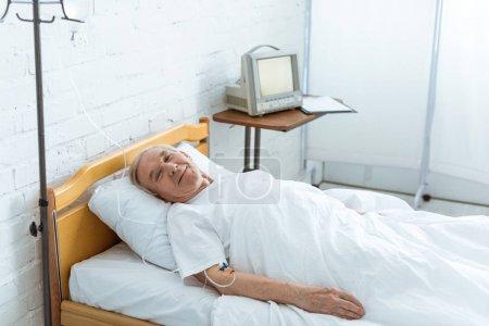 Photo pour Homme aîné malade de sourire se trouvant sur le bâti dans la clinique - image libre de droit