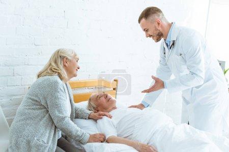 Photo pour Docteur de sourire et femme aînée près du patient malade dans la clinique - image libre de droit
