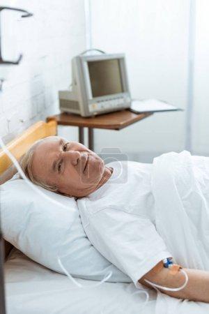 Photo pour Homme aîné de sourire malade se trouvant sur le bâti à l'hôpital - image libre de droit