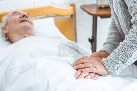 Photo pour Vue partielle de la femme aînée avec le husbend malade dans la clinique - image libre de droit