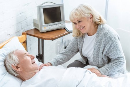 Photo pour Femme âgée souriante debout près du mari malade à l'hôpital - image libre de droit