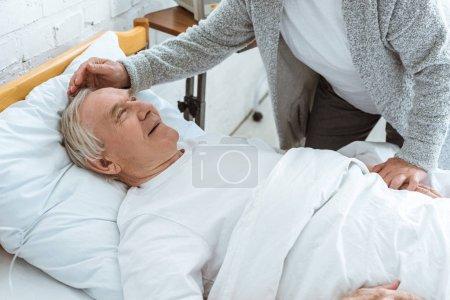 Photo pour Vue partielle de femme aînée caressant le husbend souriant malade dans la clinique - image libre de droit