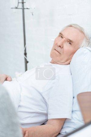 Photo pour Homme aîné malade se trouvant sur le lit et regardant la caméra dans la clinique - image libre de droit