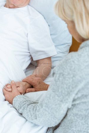 Photo for Cropped view of senior woman holding hands with sick husband in hospital - Royalty Free Image