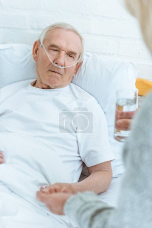 Photo pour Vue recadrée de femme aînée donnant le verre de l'eau au mari malade à l'hôpital - image libre de droit
