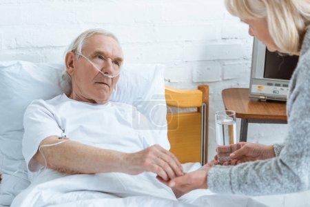 Ausgeschnittene Ansicht einer Seniorin, die kranken Ehemann im Krankenhaus ein Glas Wasser gab