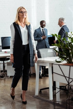 Photo for Selective focus of attractive blonde businesswoman walking on office near multicultural men - Royalty Free Image