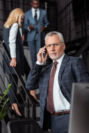 Photo for Selective focus of handsome businessman in glasses talking on smartphone near multicultural partners - Royalty Free Image