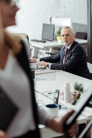 Photo for Selective focus of businessman in glasses looking at woman in office - Royalty Free Image