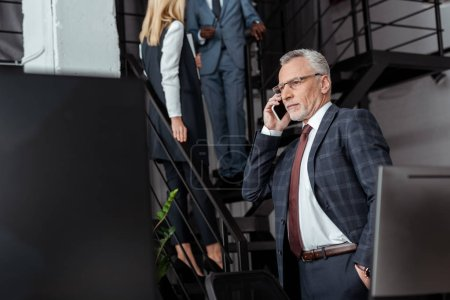 Photo for Selective focus of businessman talking on smartphone near multicultural partners - Royalty Free Image