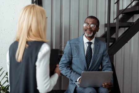 Photo for Selective focus of cheerful african american man in glasses looking at blonde woman while using laptop - Royalty Free Image